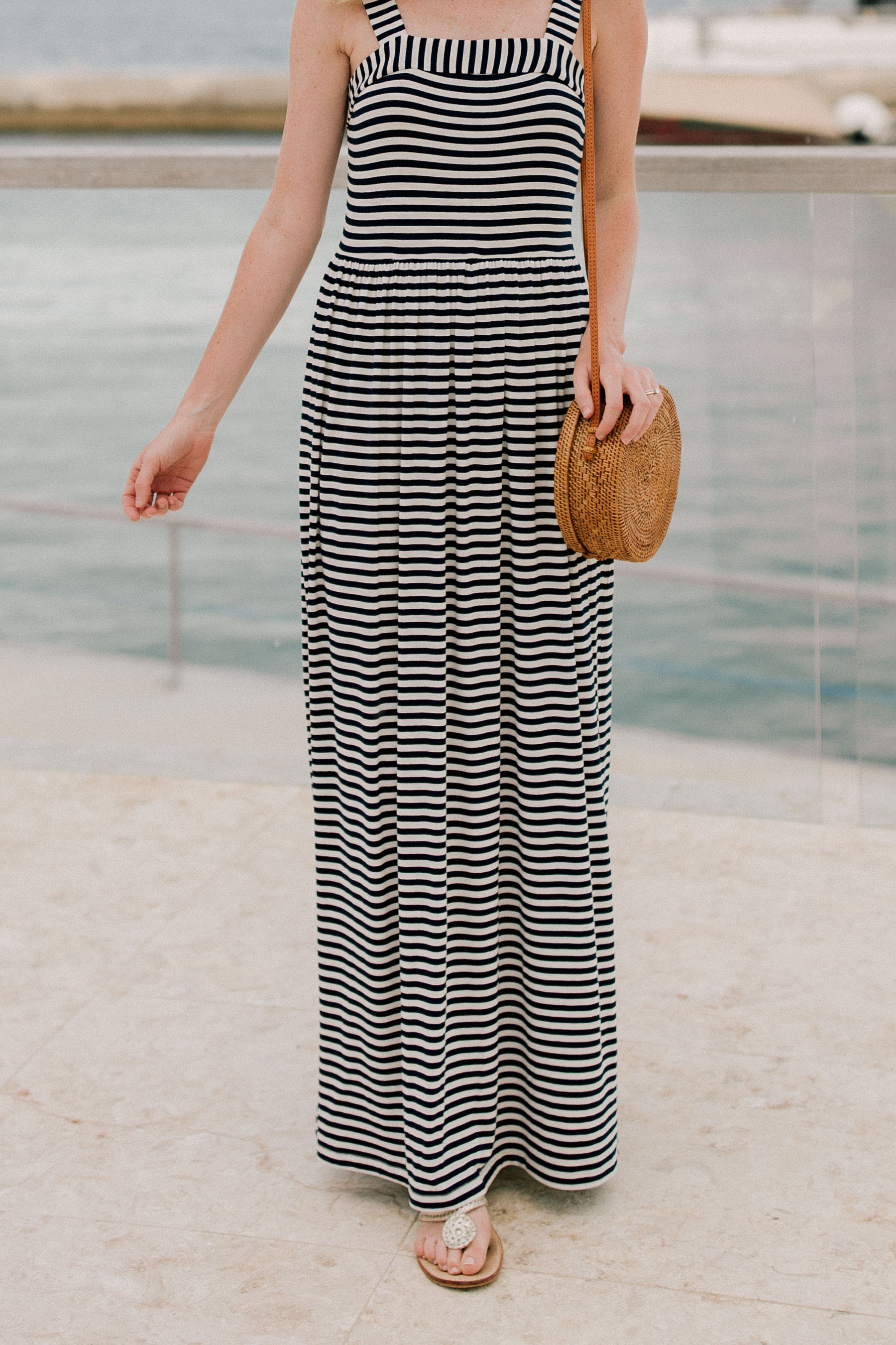 Kelly is wearing a Navy Striped Maxi Dress of Loft and a wove bag