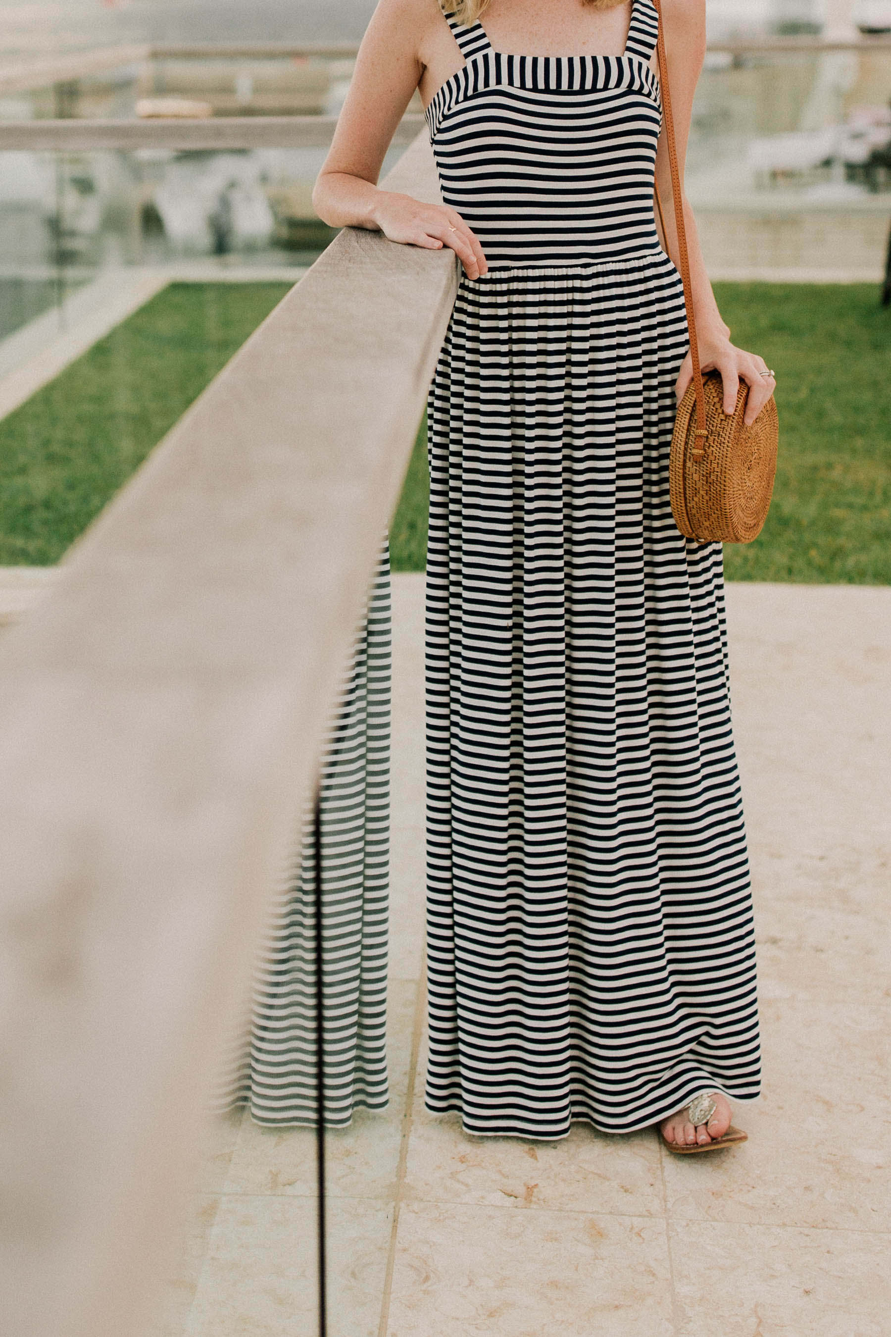 Kelly is wearing a Navy Striped Maxi Dress of Loft and a wove bag in Bermuda