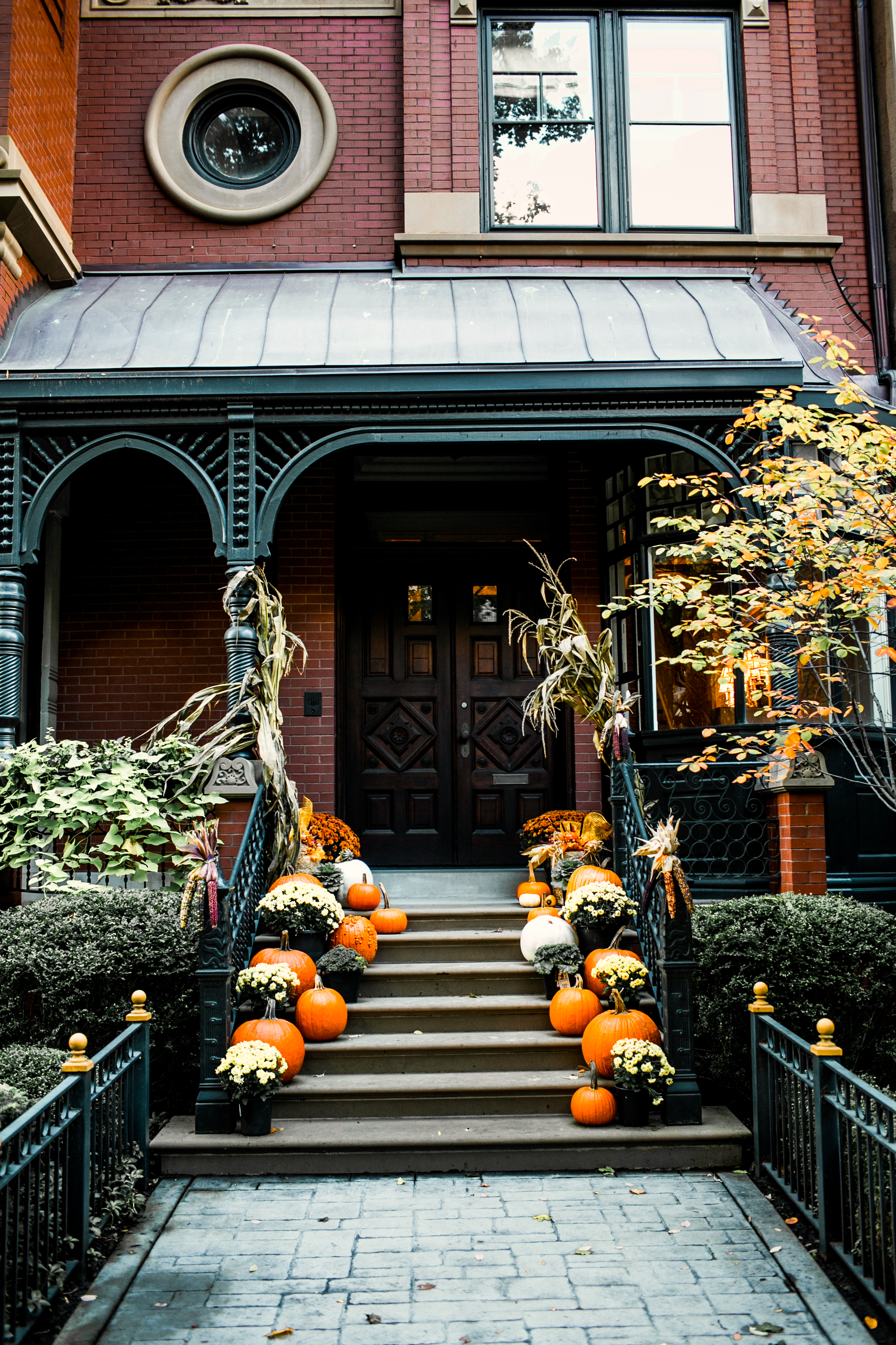 A beautiful stoop filled with pumpkins and mums.