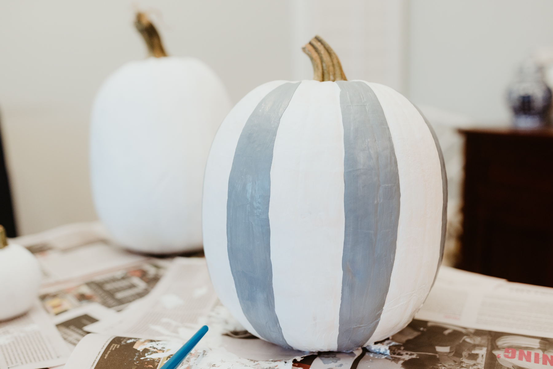Buffalo plaid pumpkin: On a paper plate, mix the white and black paint to create your desired shade of gray. Then paintvertical stripes following the natural lines of the pumpkin. These lines aren't spaced out perfectly, so don't think of them as borders. Simply use them as guides!