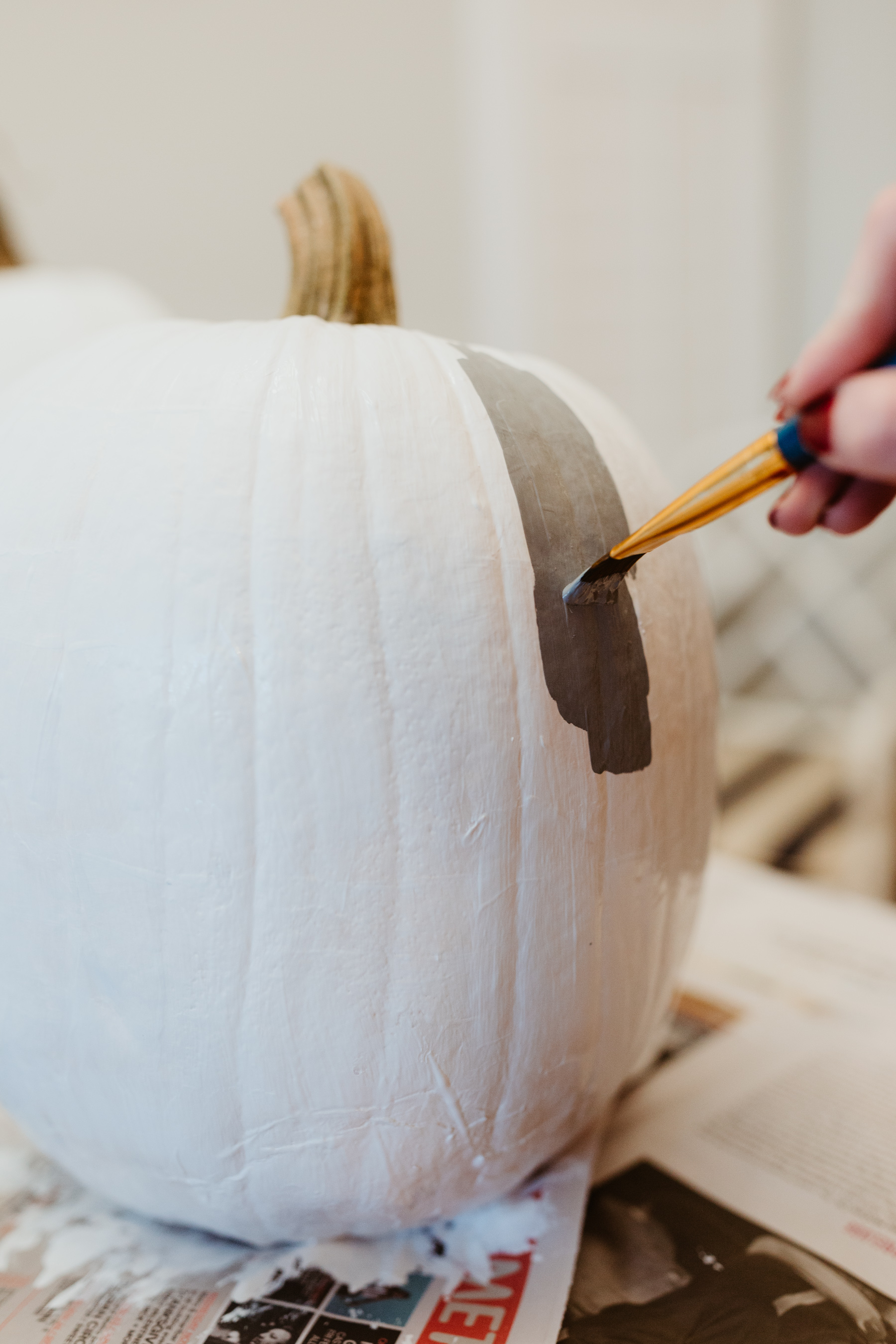 Buffalo plaid pumpkin: Start by painting the pumpkin white. We used acrylic paint we found on Amazon.