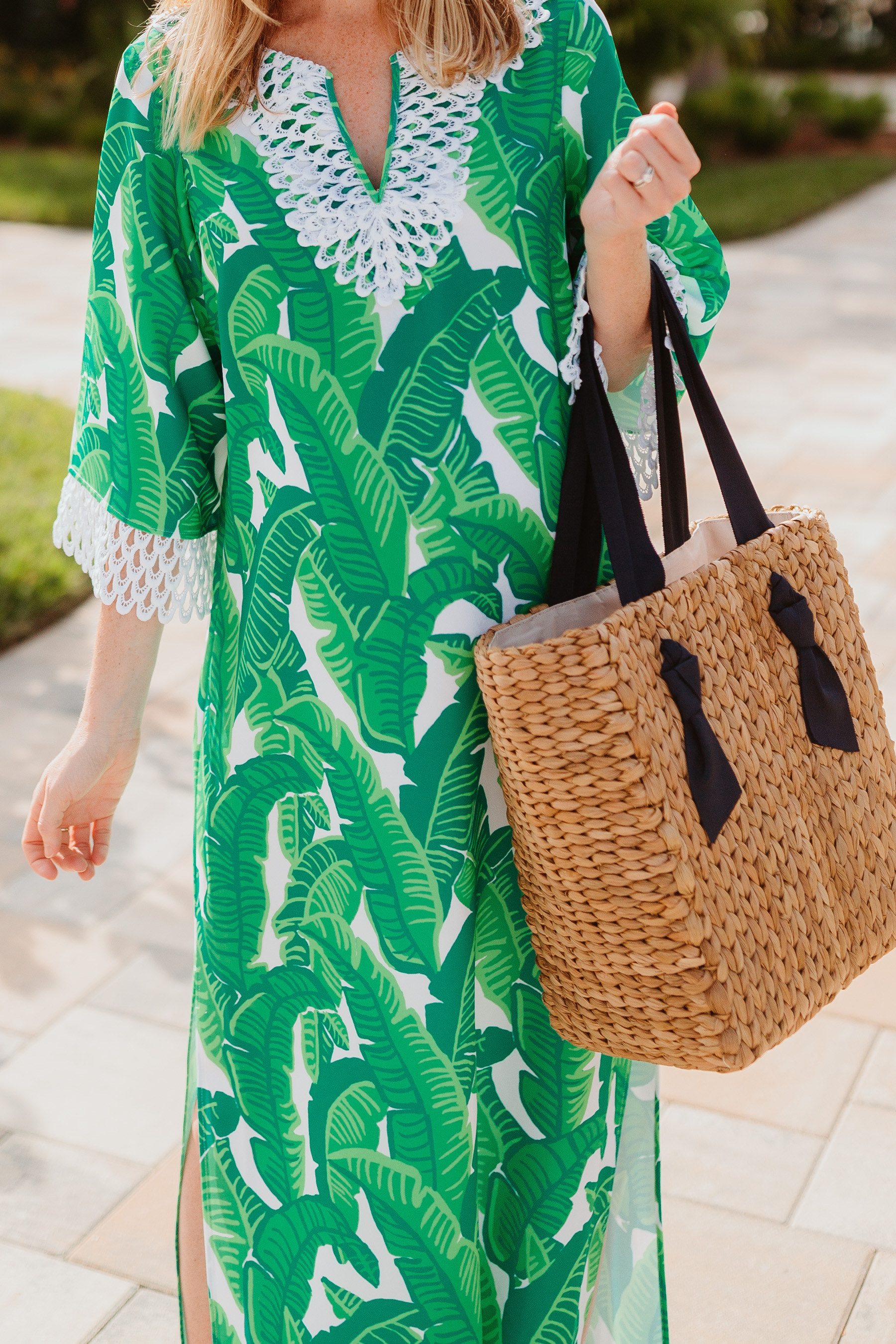 Kelly is wearing a Sail to Sable Banana Leaf Palm Dress / Pamela Munson Woven Tote