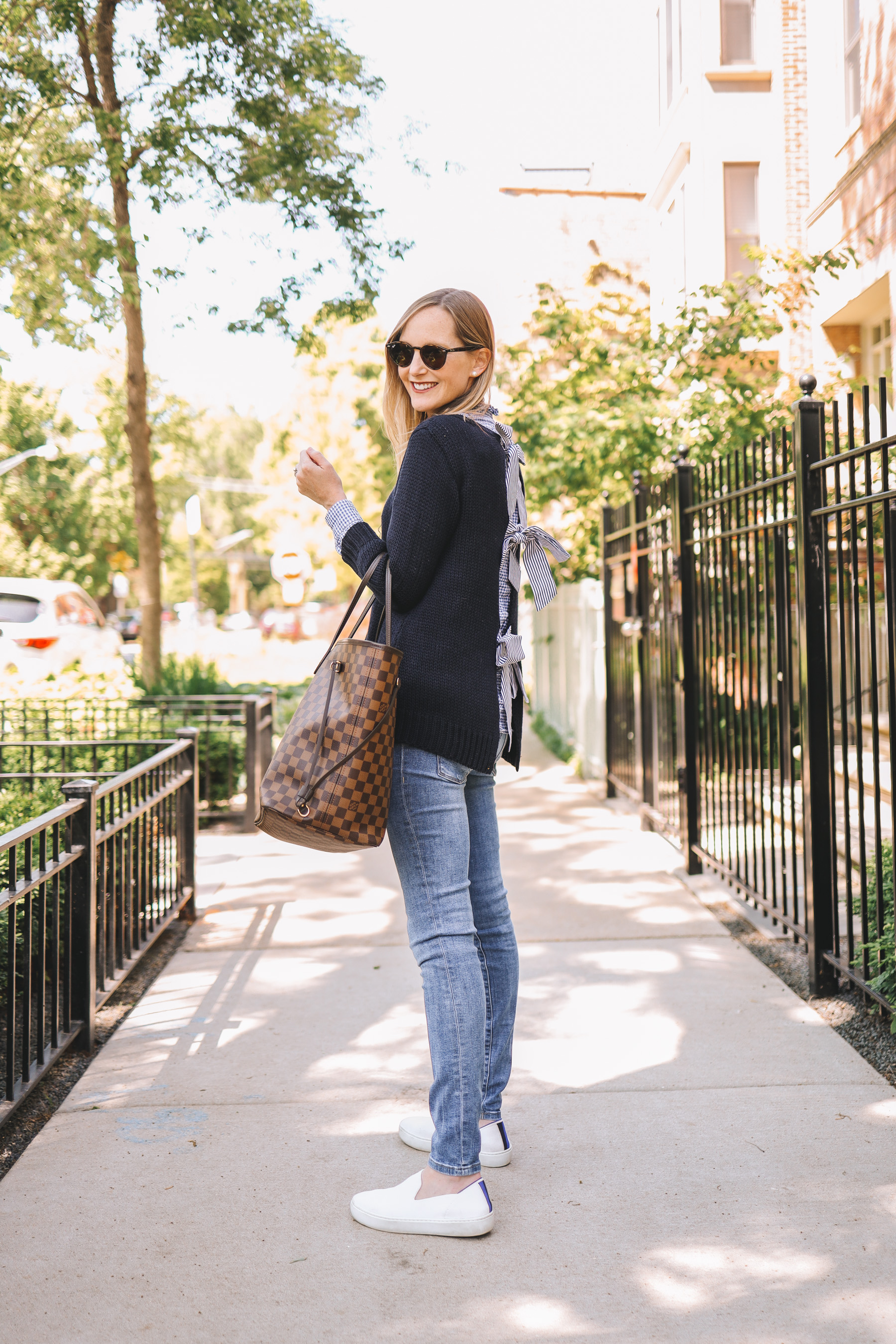 Kely's outfit details: Maternity Jeans / Rothy's Washable Sneakers / Tuckernuck Bow Sweater / J.McLaughlin Gingham Button-Down / Louis Vuitton Neverfull GM /  Ray-Ban Sunglasses