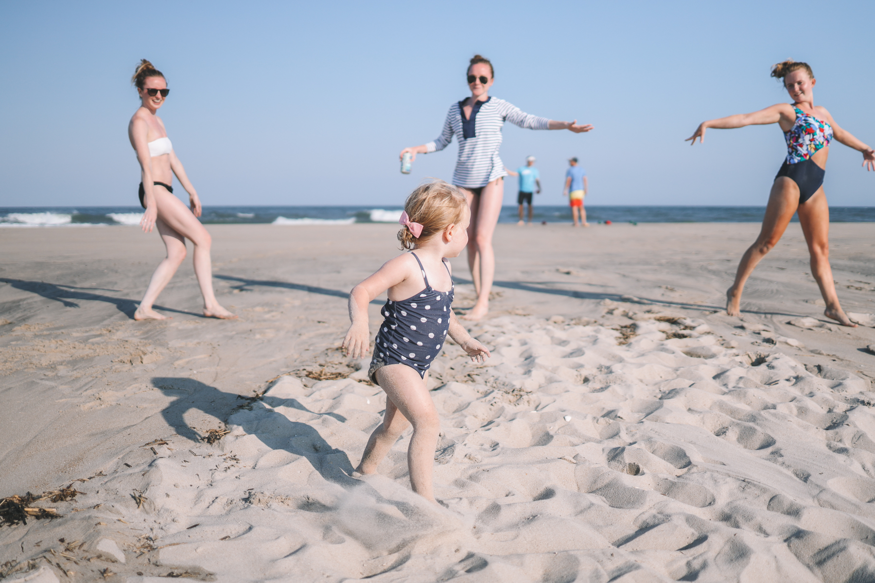 Emma is running in the sand, her cousins pictured in the background