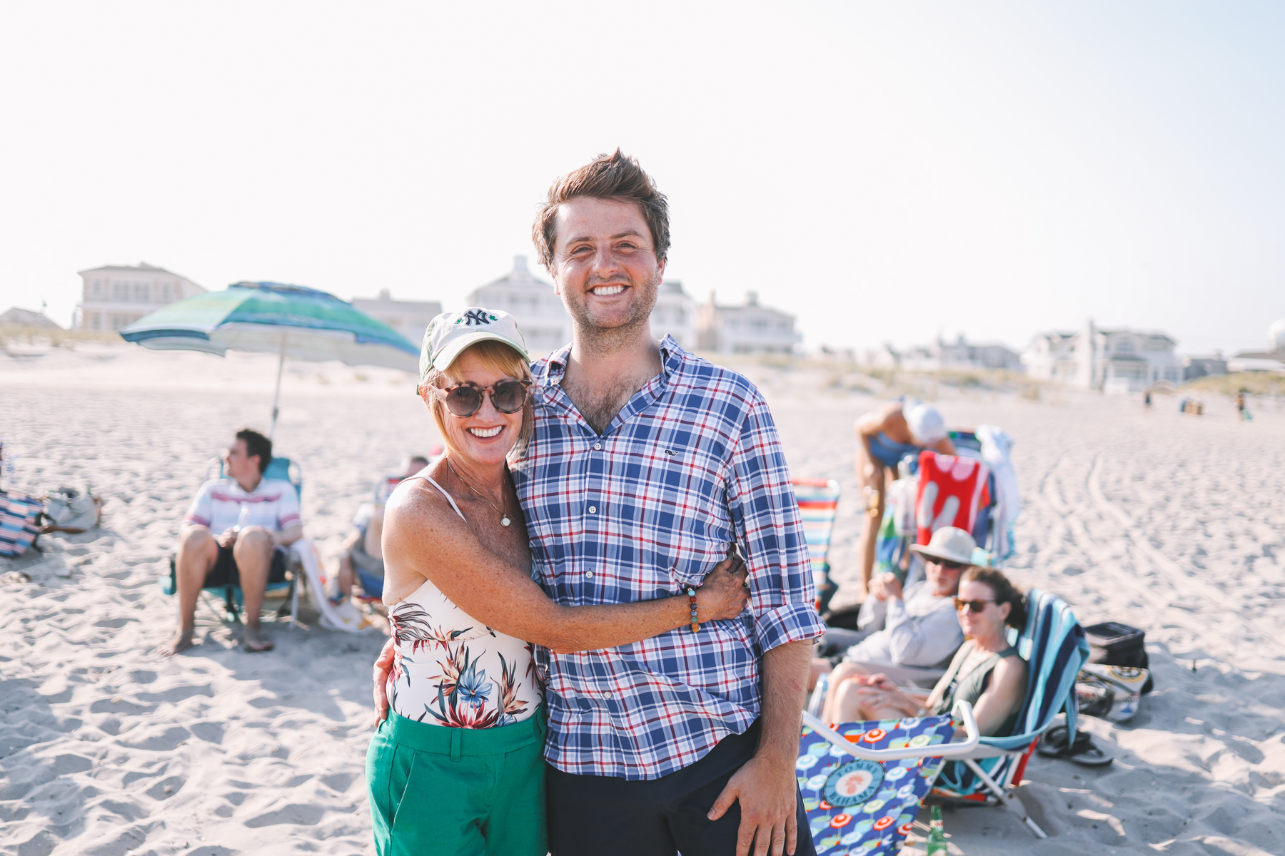 A female in a white shirt and green shorts is smiling next to a man in a plaid shirt