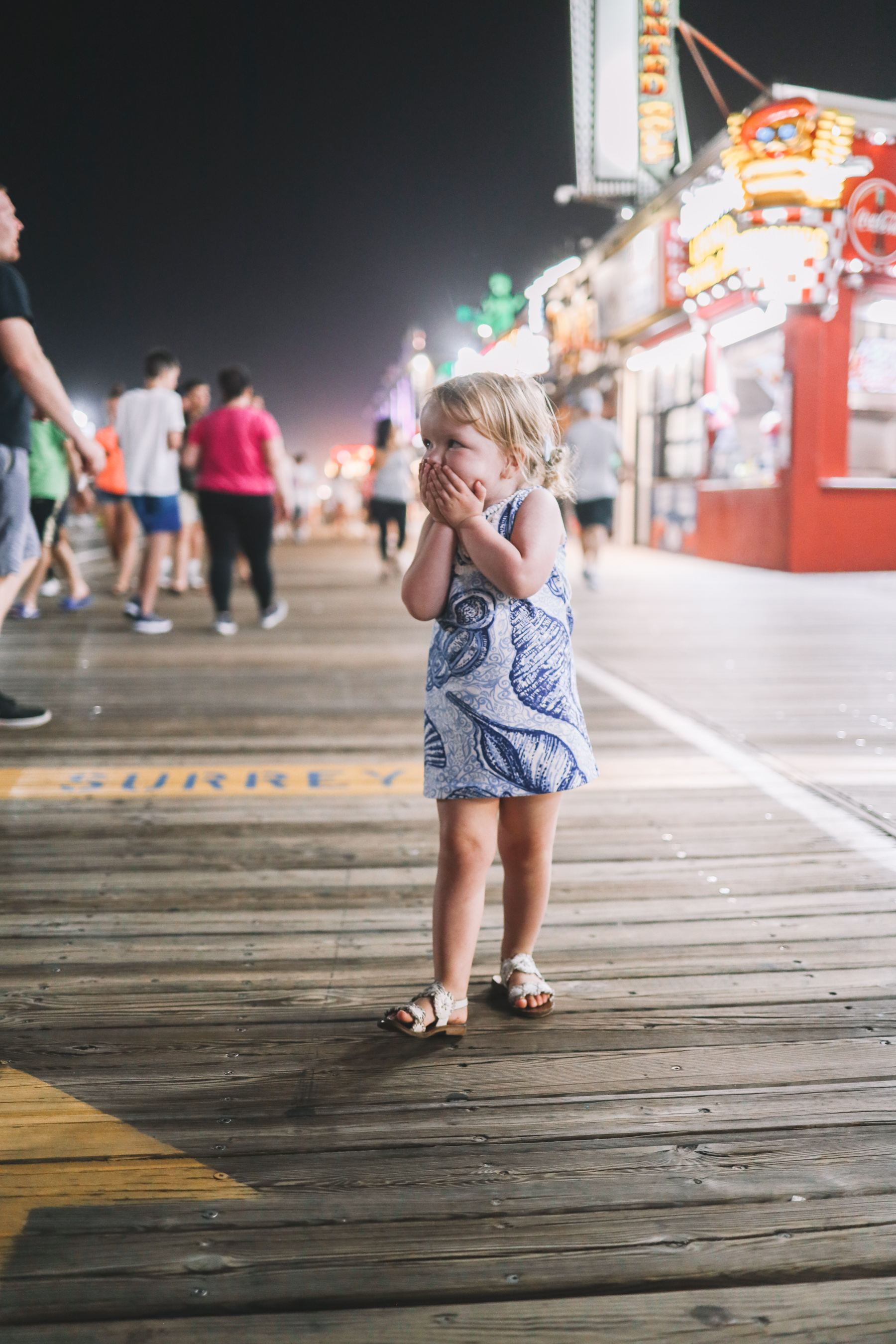 Emma giggles and covers her mouth while walking down the pier