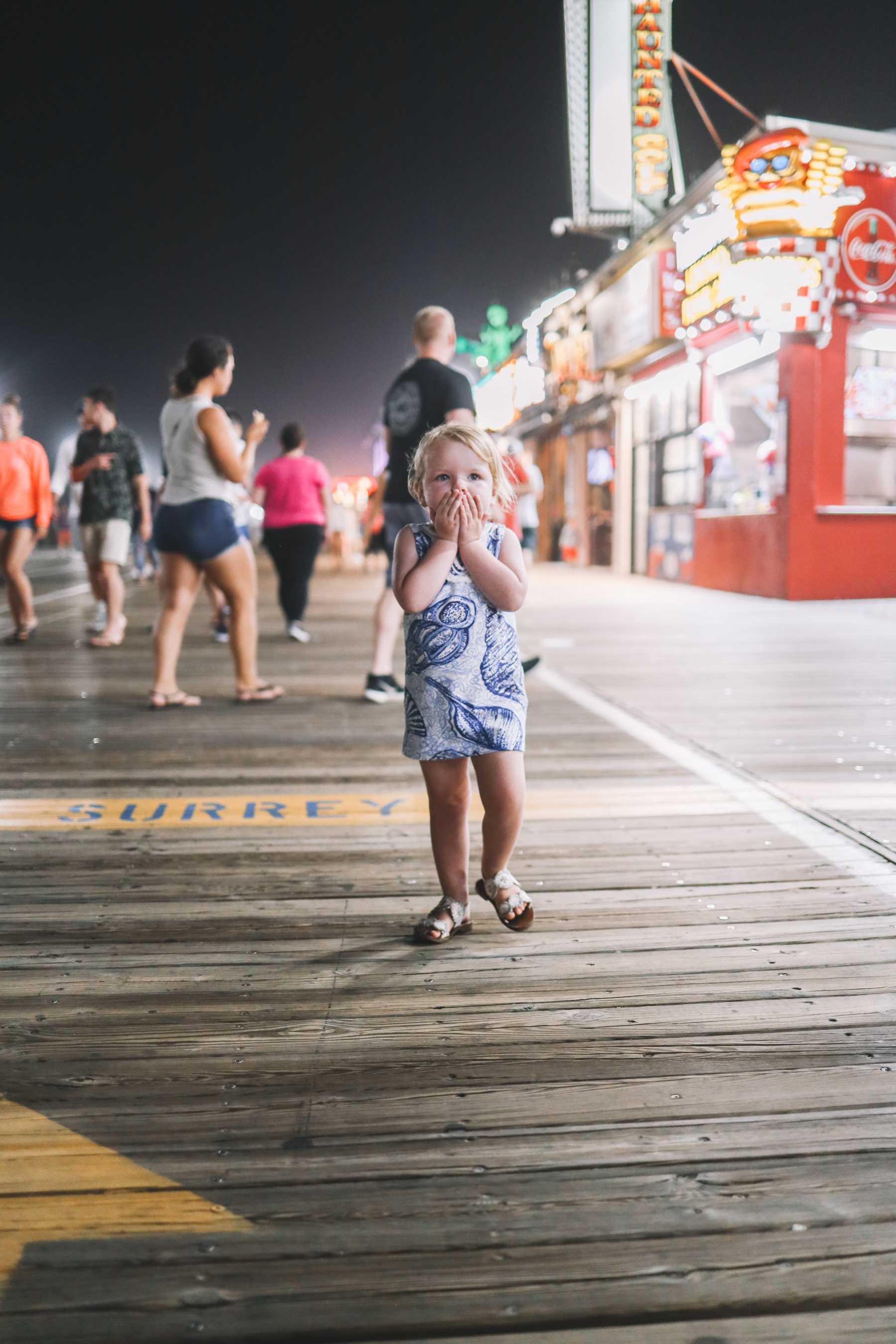 Emma giggles and covers her mouth while walking down the pier, facing head on