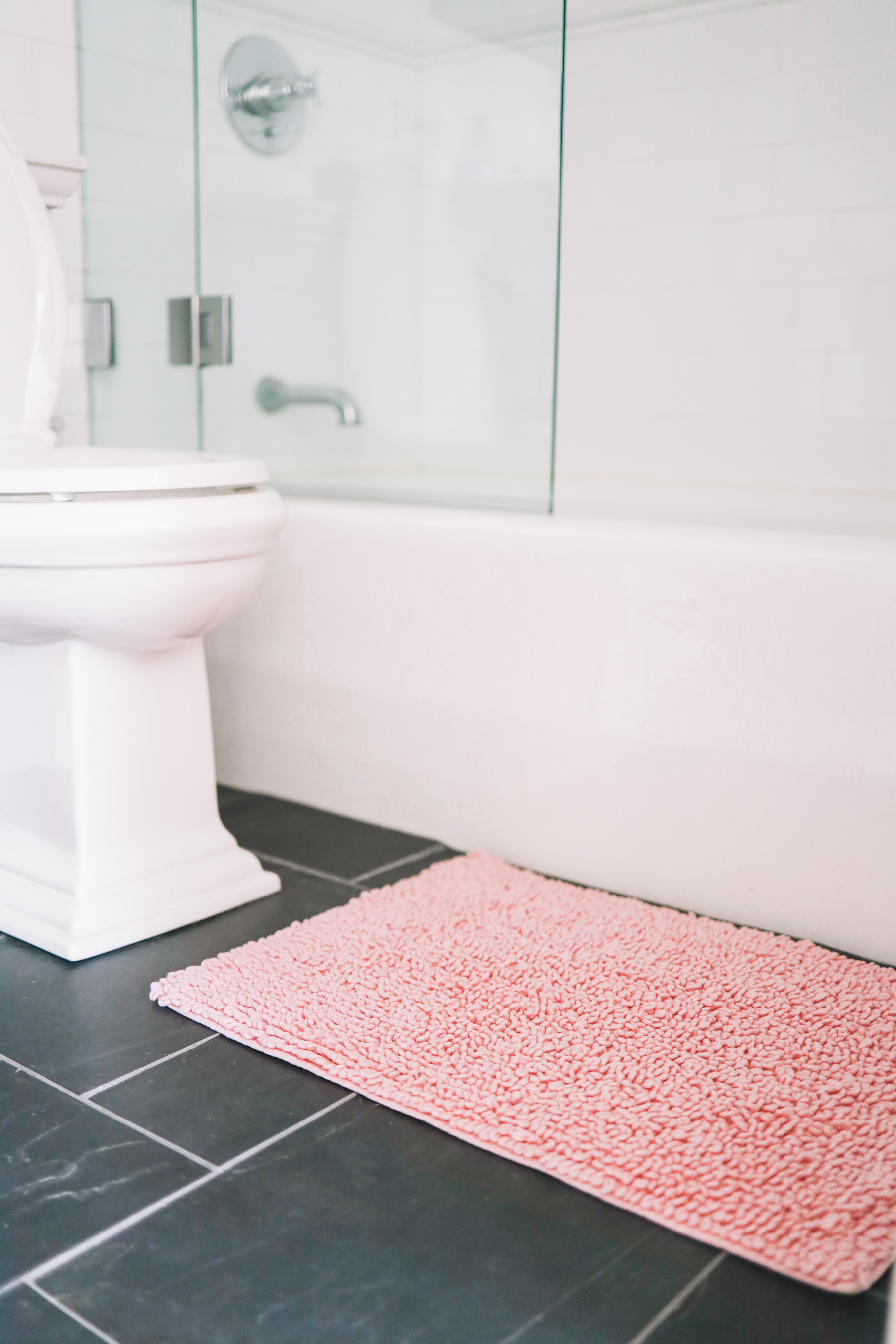Preppy Girls Room - Pink bathmat contrasted by a black tiled floor and a white toilet and white bathtub