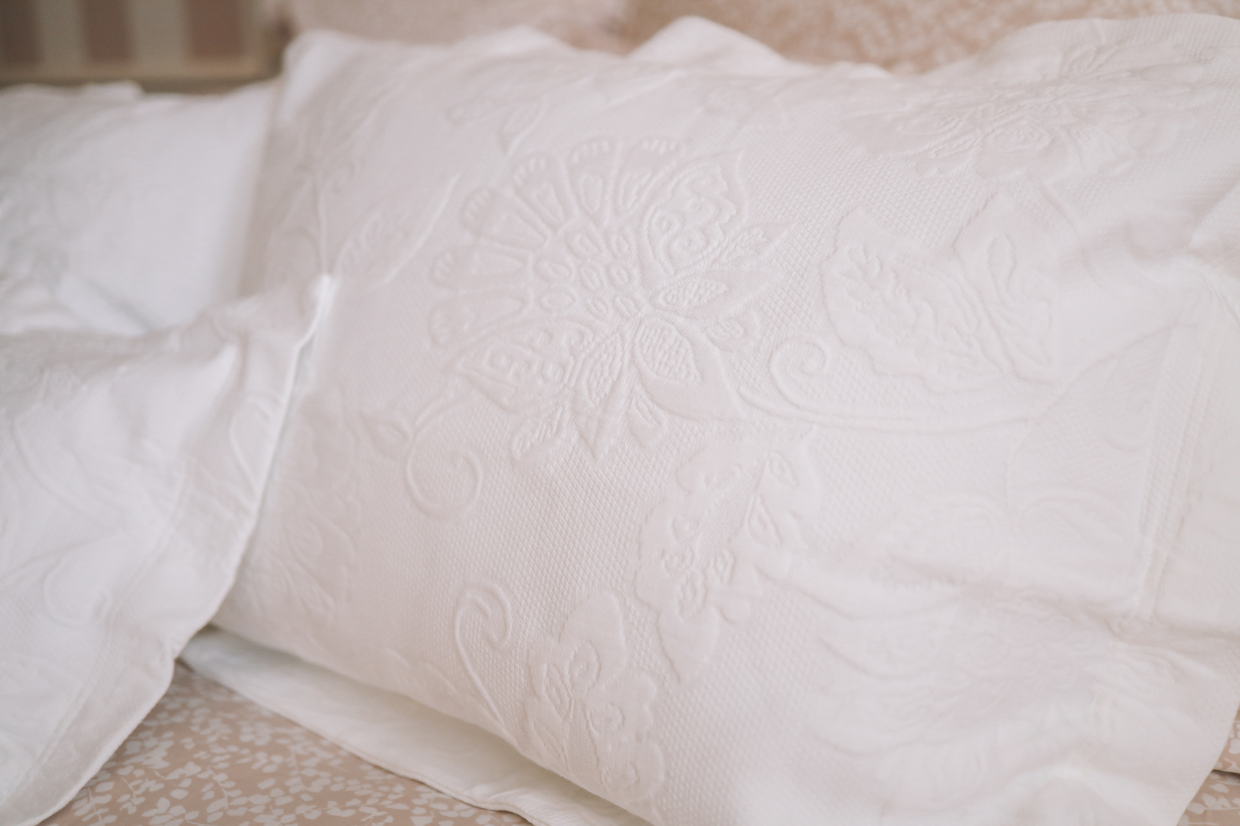 White pillows on pink bed sheets