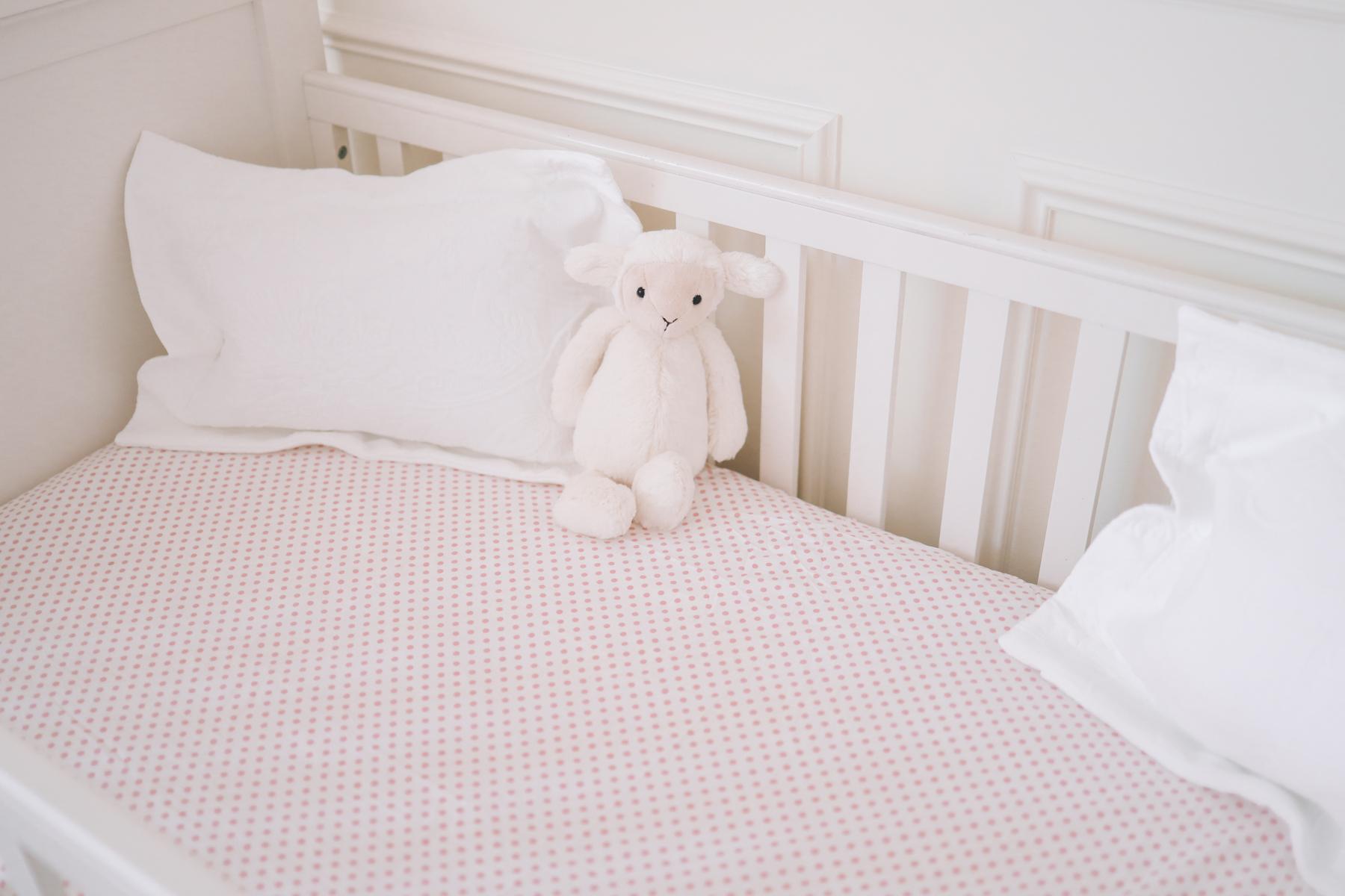 Preppy Girls Room - A monkey stuffed animal in a baby crib
