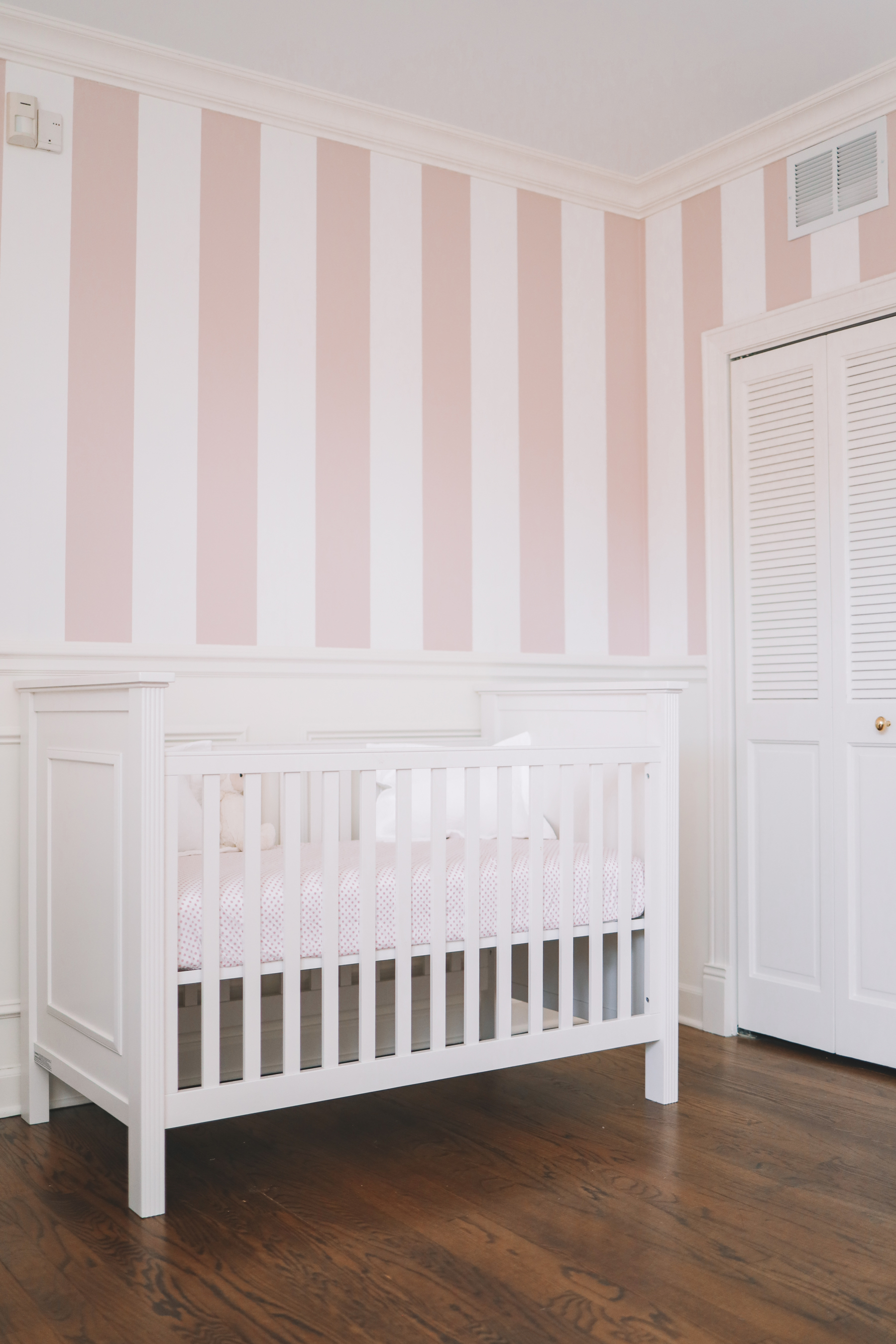 Preppy Girls Room - A white crib with pink and white stripped wallpaper