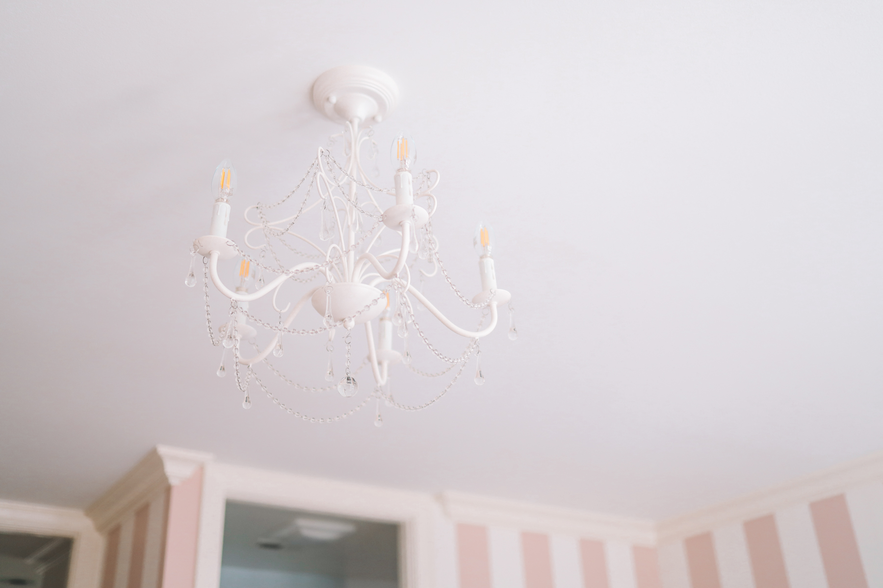 Preppy Girls Room - A white chandelier with a white roof and wallpapered walls