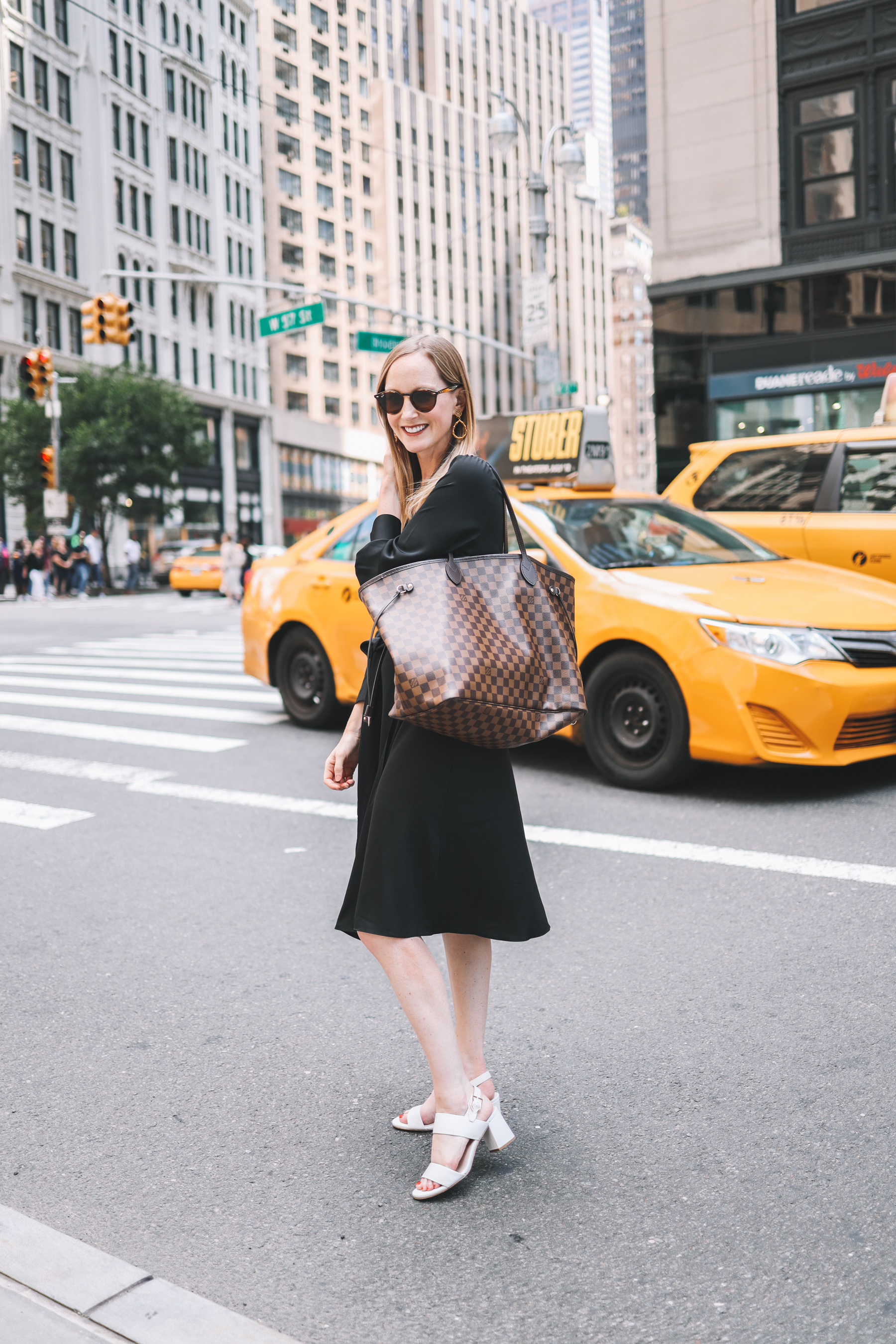 Kelly wearing a black wrap dress and holding a Louis Vuitton purse with a yellow, New York City yellow cab in the background