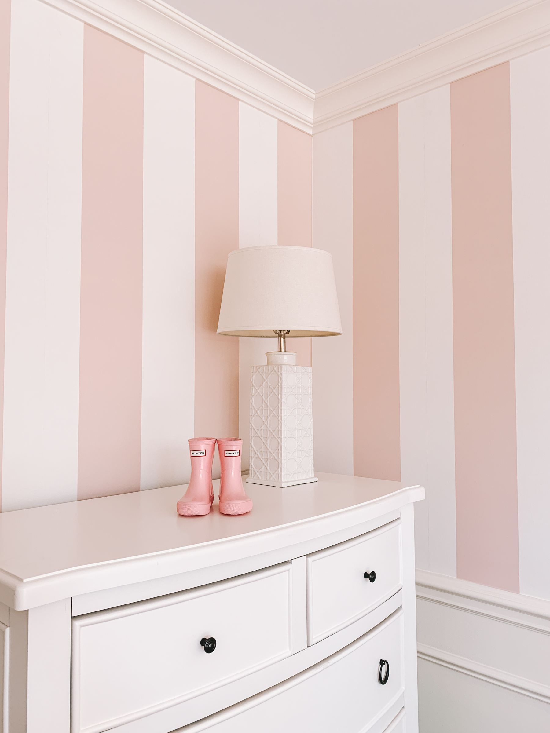 Pink baby Hunter boots are displayed on top of white dressed with pink-stripped wallpaper in the backdrop