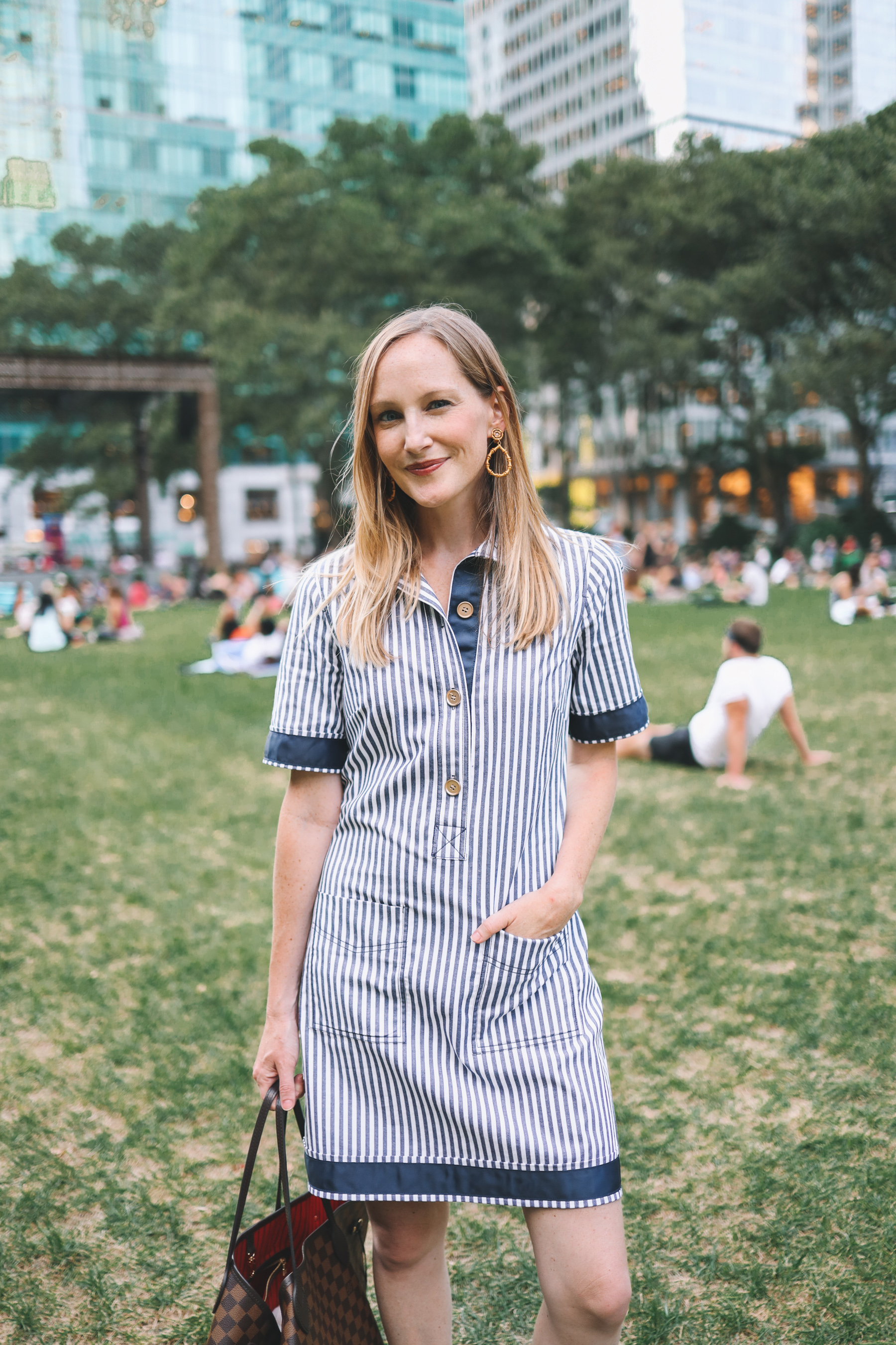 Kelly smiling in her easy shirtdress while spending time in the city