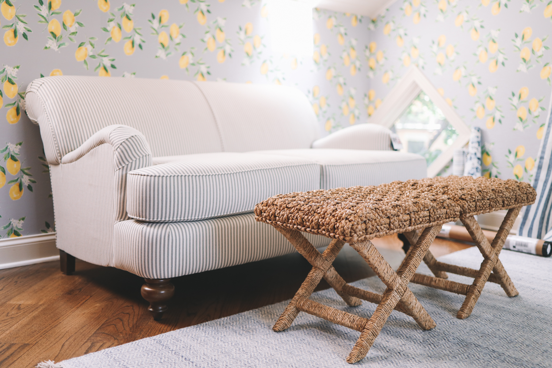 A custom striped loveseat for under $600 is next to a woven coffee table and lemon wallpaper in Kelly Larkin's living room