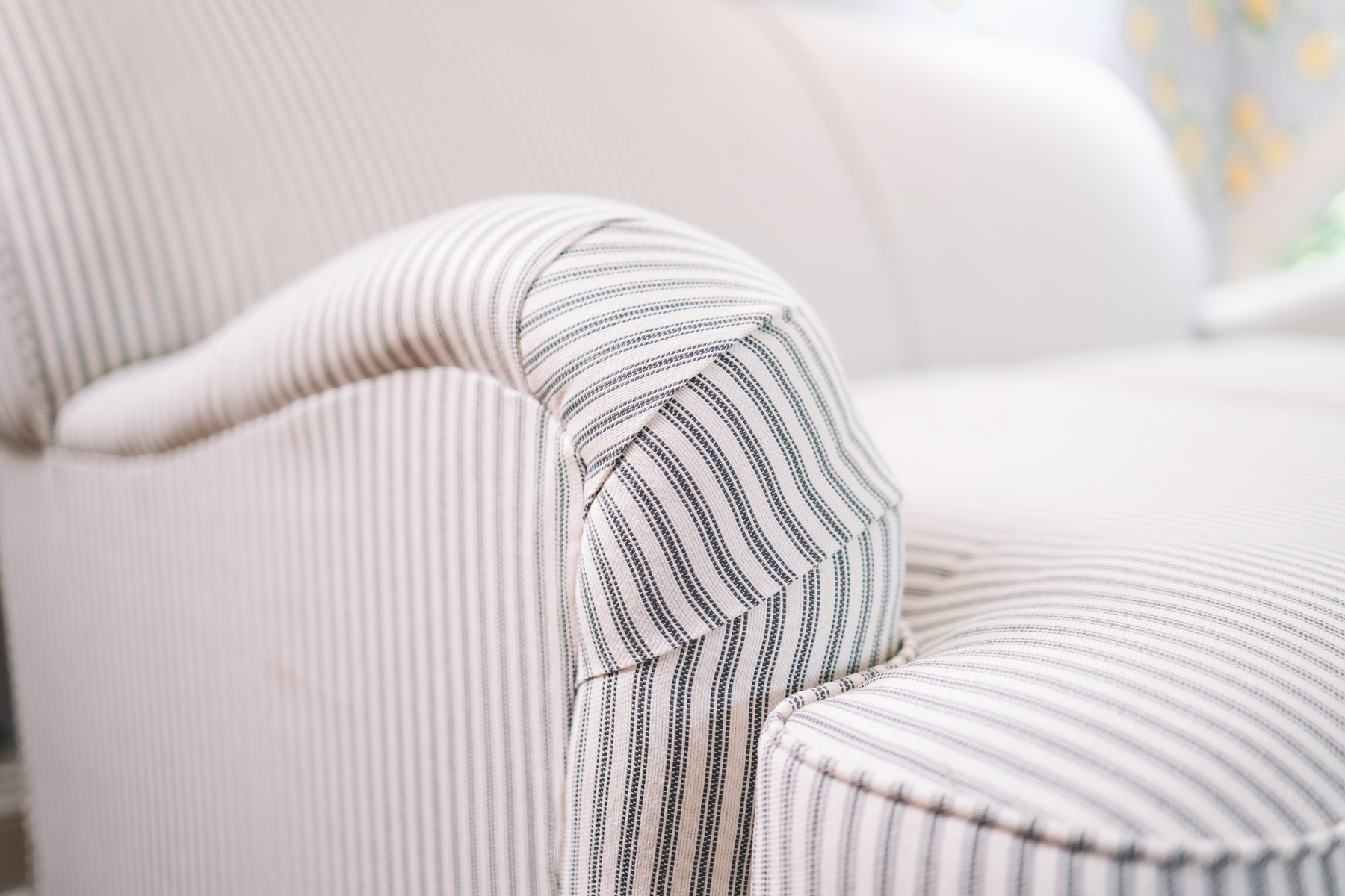 Up close shot of the custom striped loveseat, prices ranging from just under $600 to more, depending on customization