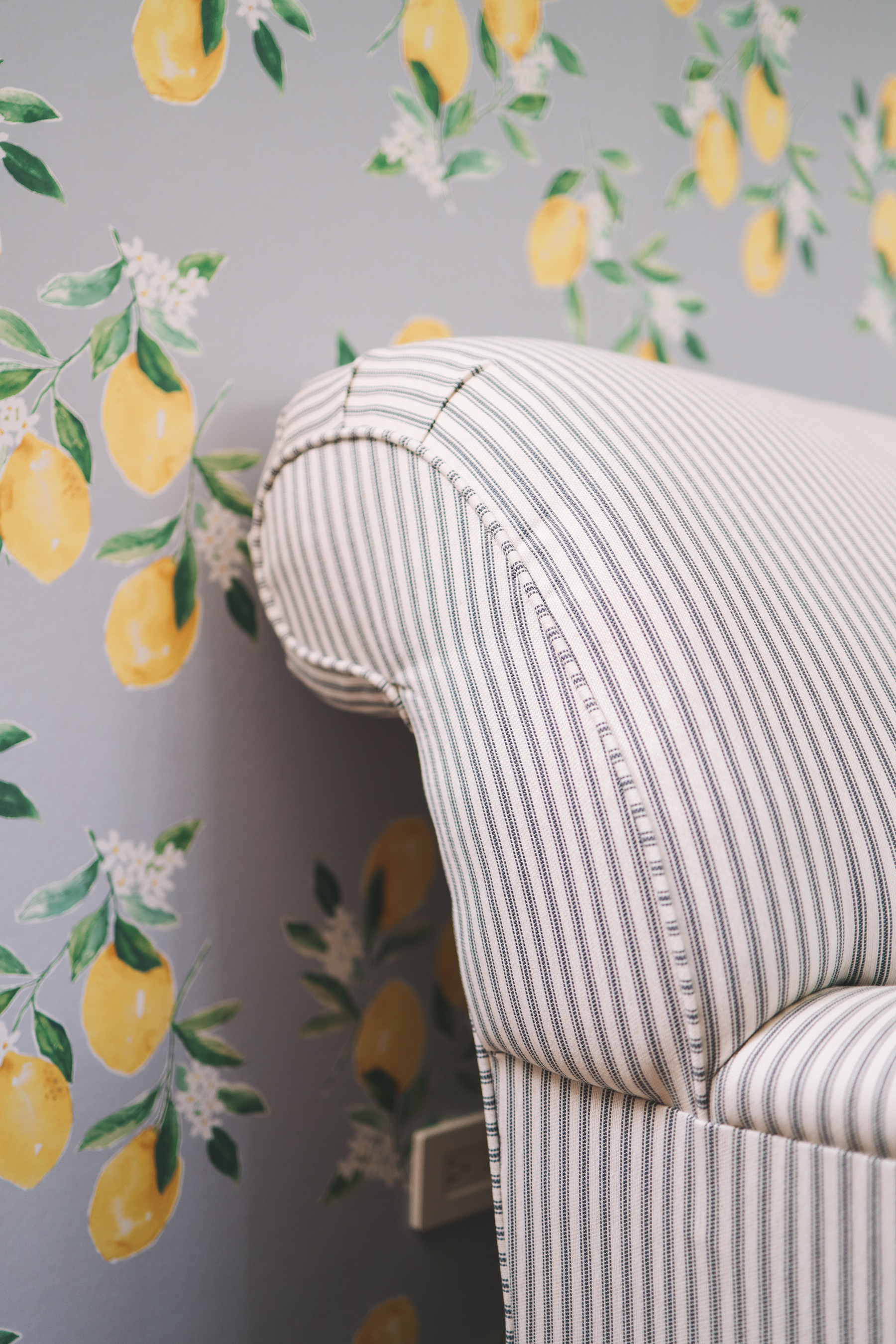 A lemon wallpaper adds a zest to the stripes in the loveseat