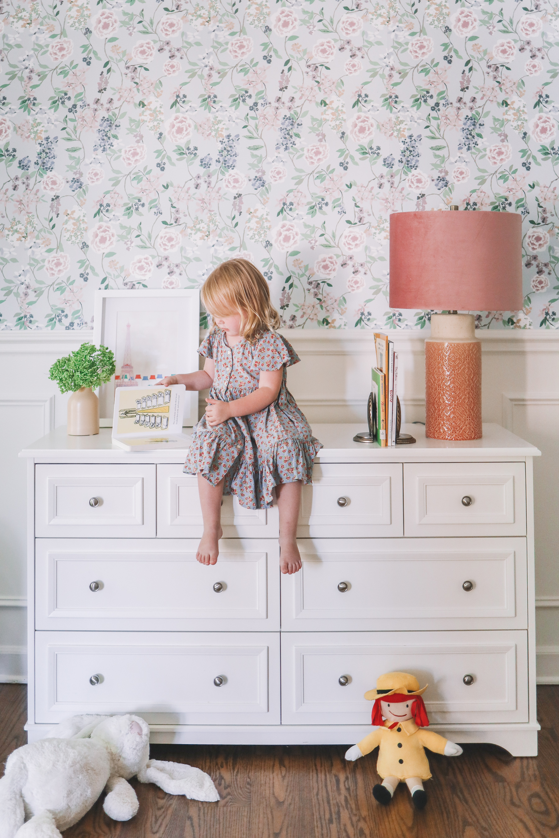 flower home of this little girl who is sitting on a dresser