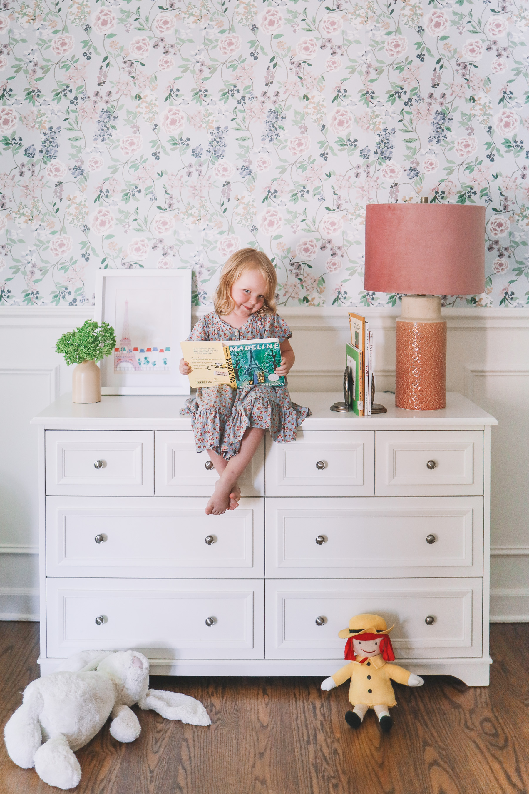 a little girl on a white dresser who is reading