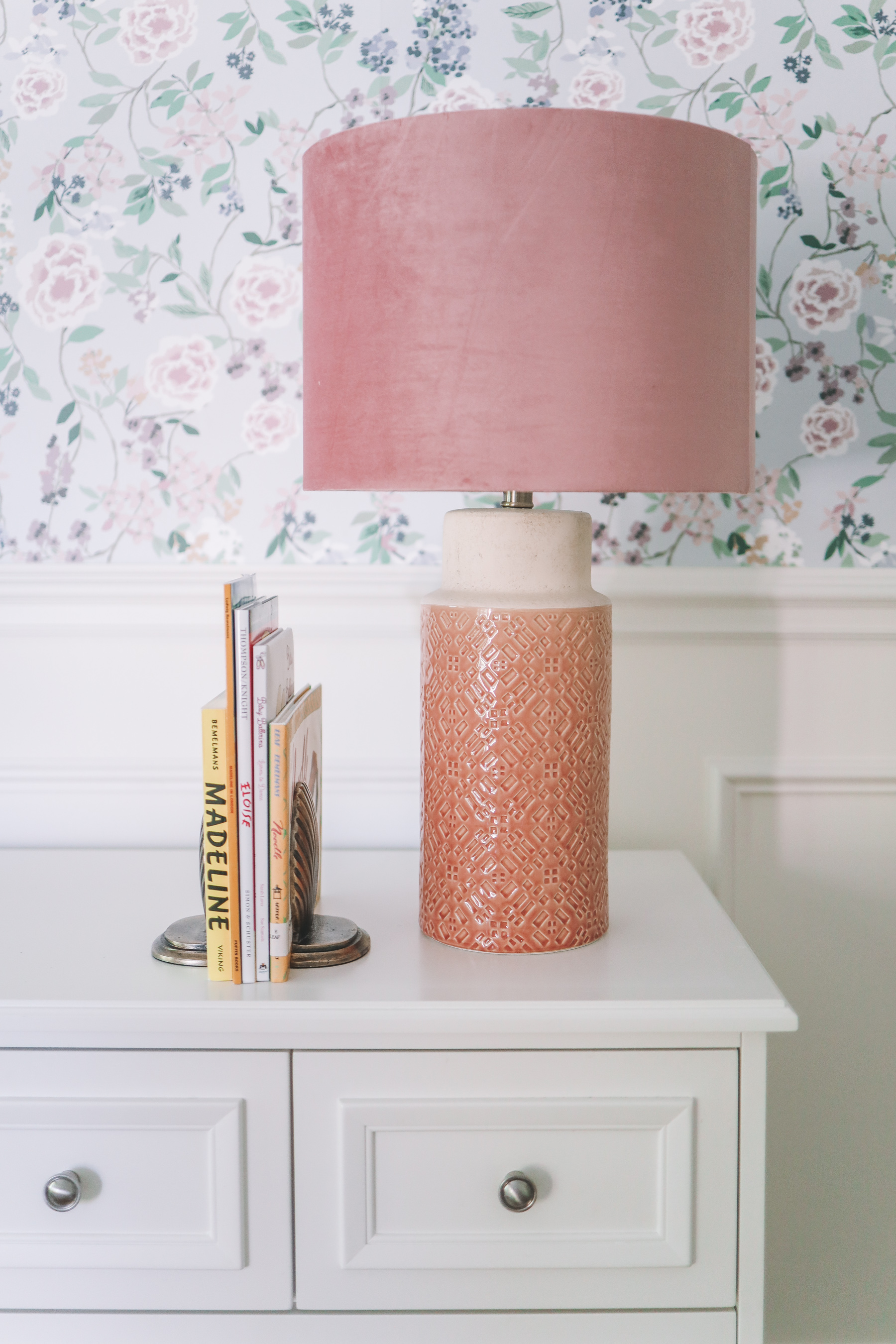 a white dresser with a pink lamp