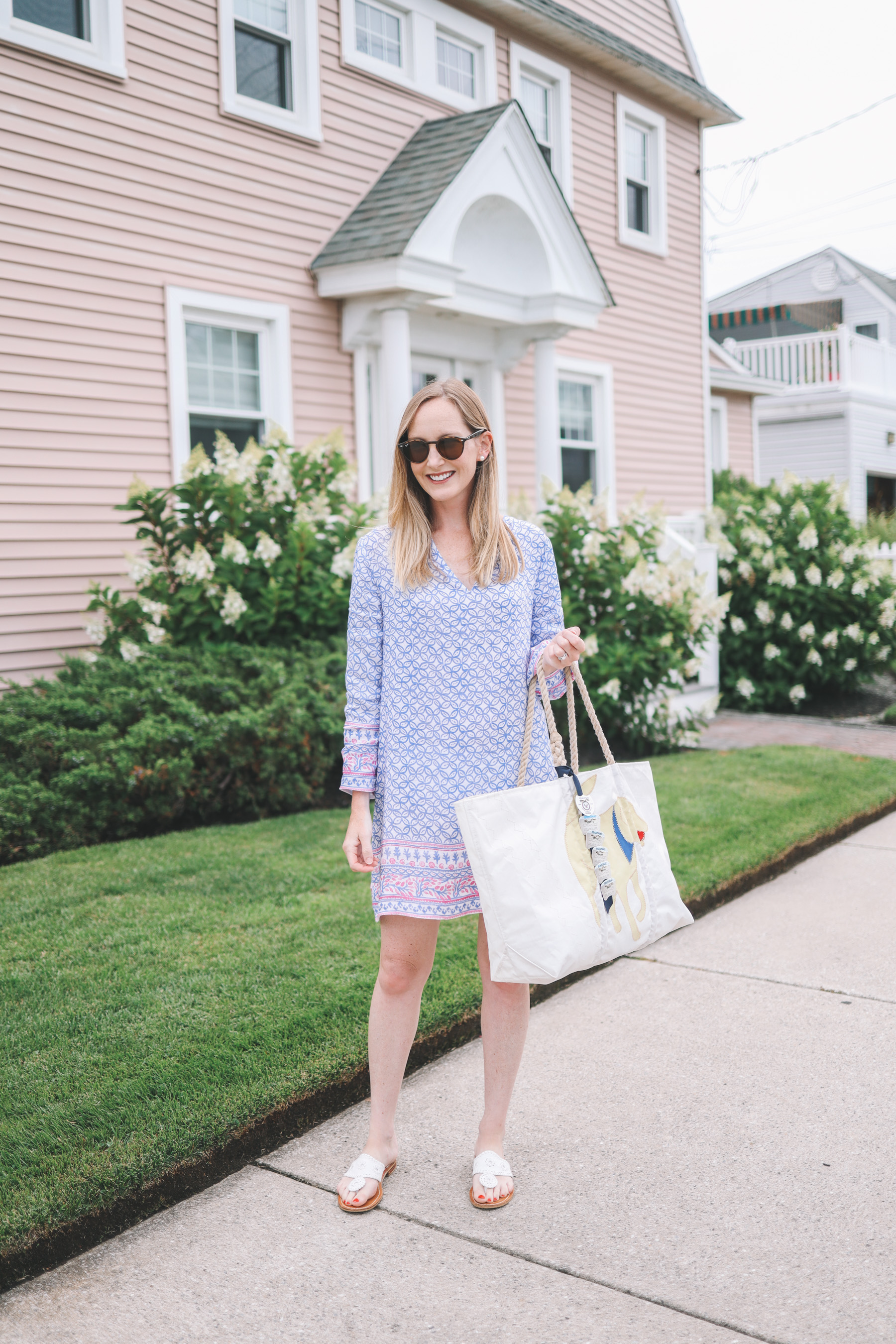 Kelly holds a beach tote in front of a salmon-colored house in Jersey