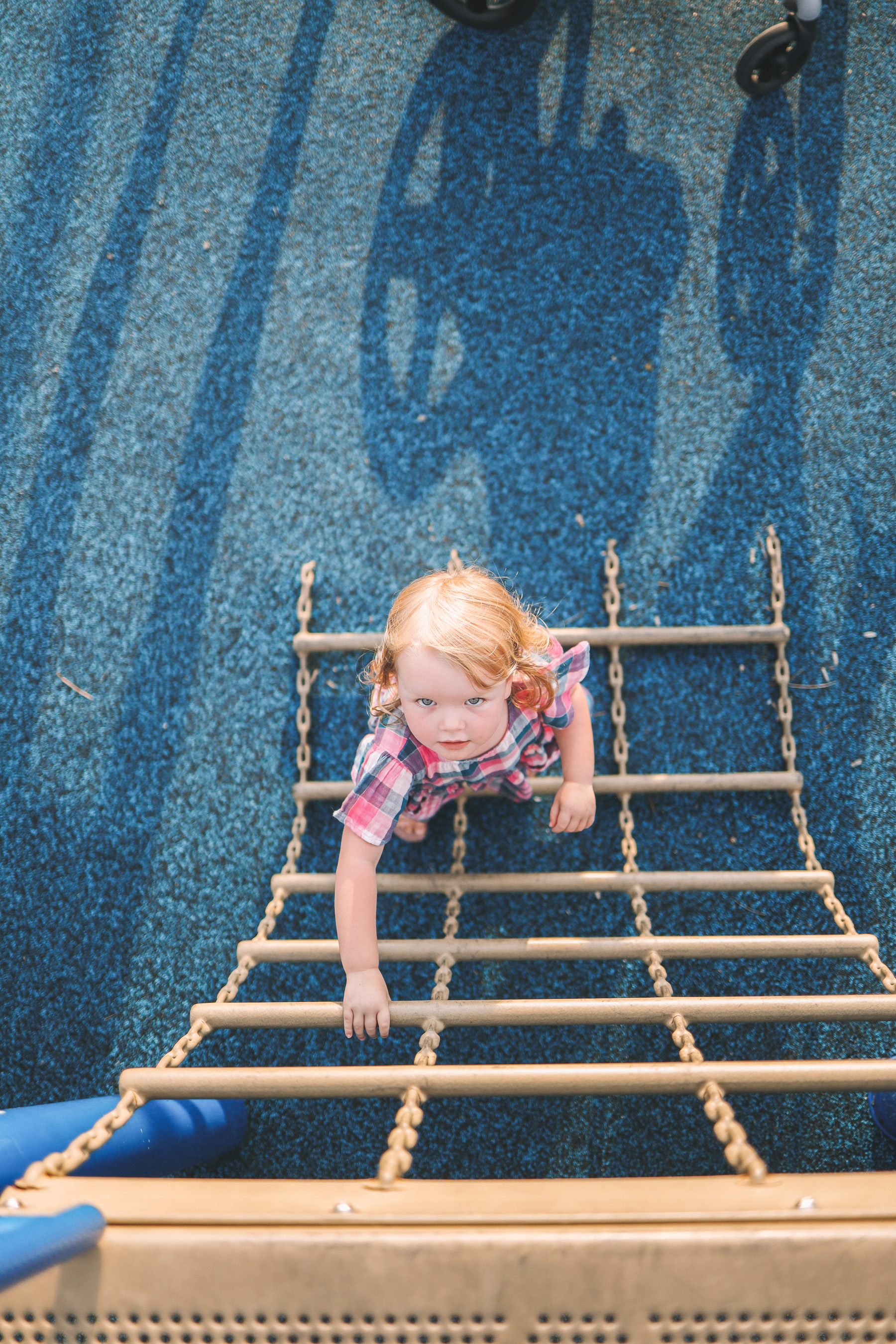 The toddler girl climbs up the playground