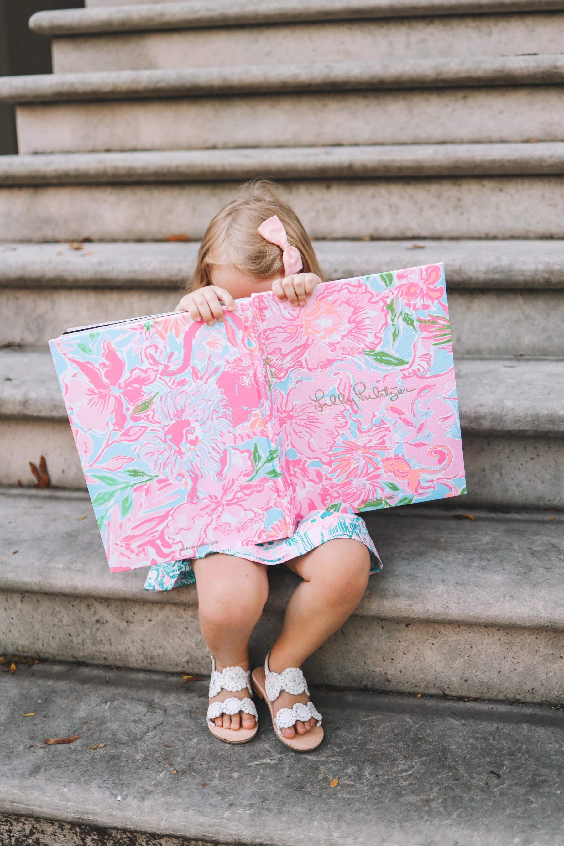 a girl hiding behind a floral book
