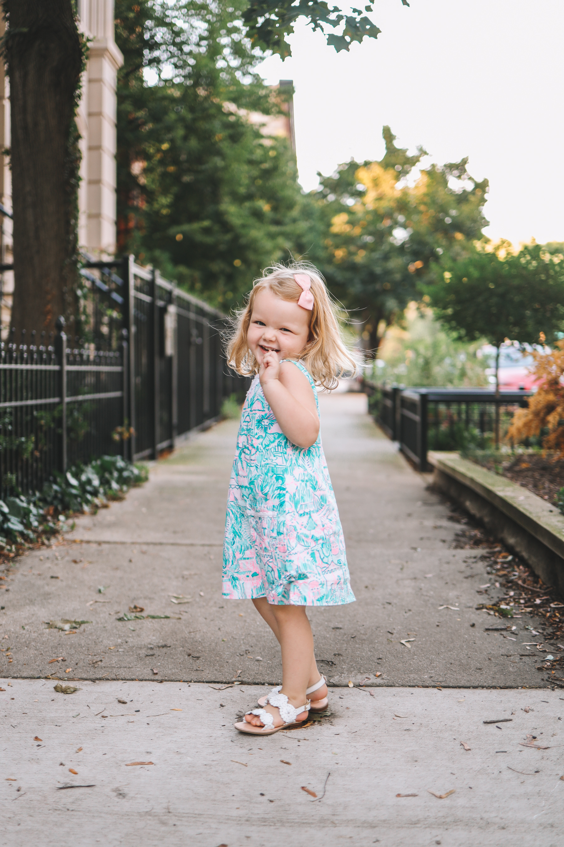 a little girl smiling in a dress