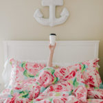 the lily pulitzer after party sale is pictured with a coffee and flowery sheets in a bedroom