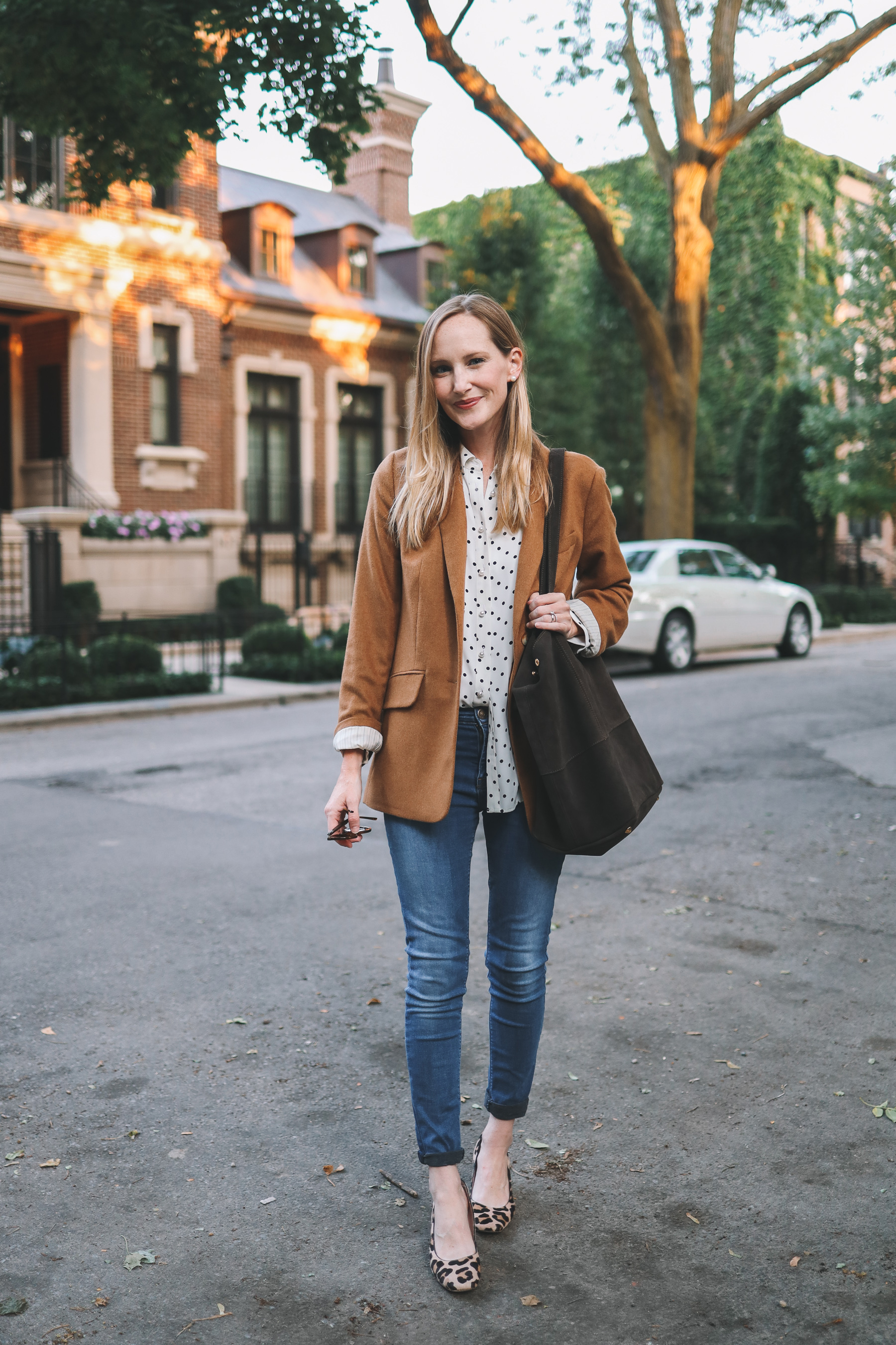 a woman in a brown jacket and a polka dot shirt wearing a leather tote bag