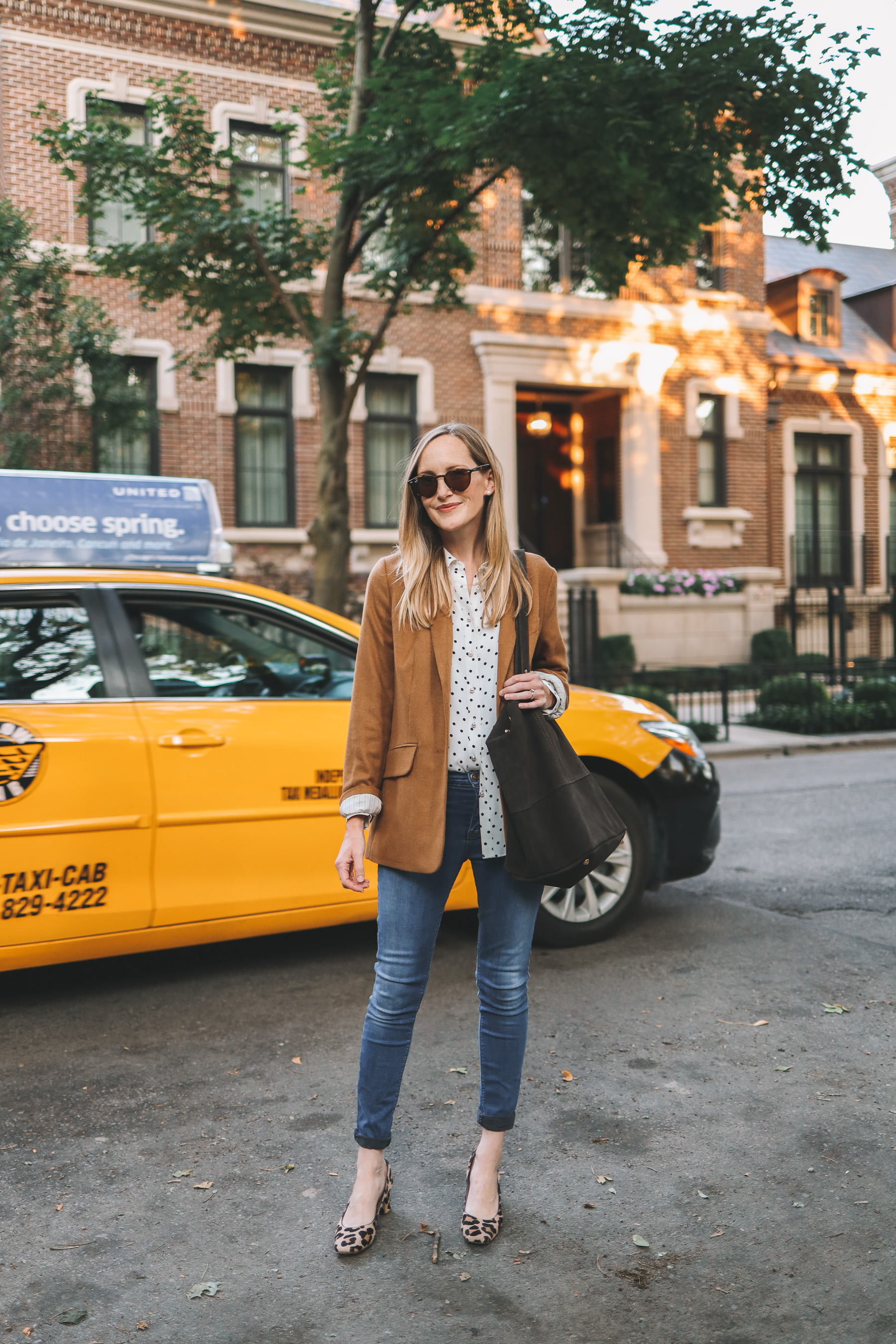 a girl in the street wewaring a Mark & Graham Amalfi Italin Suede Tote and a yellow cab in the back
