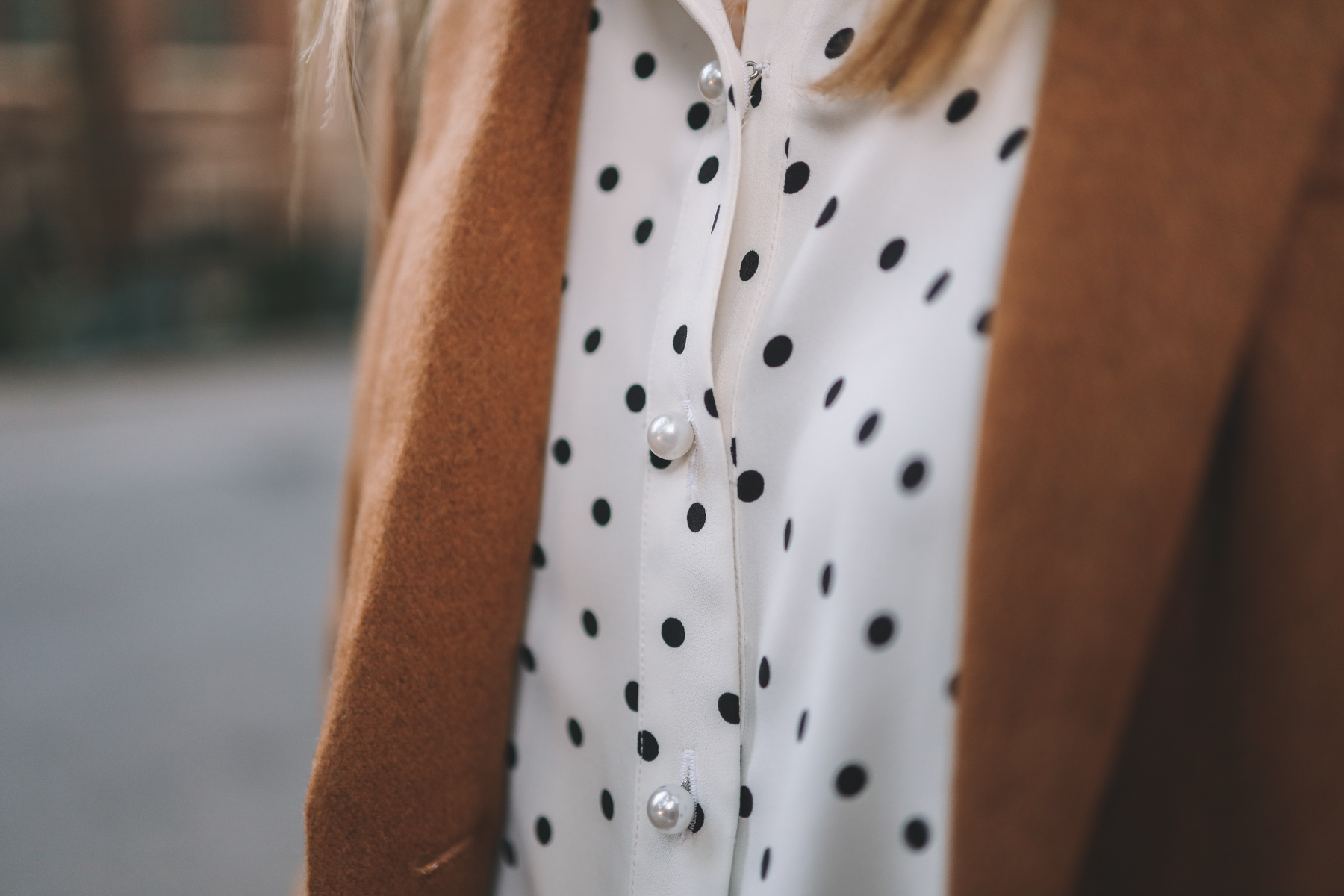 an up close of a polka dot button down with pearls