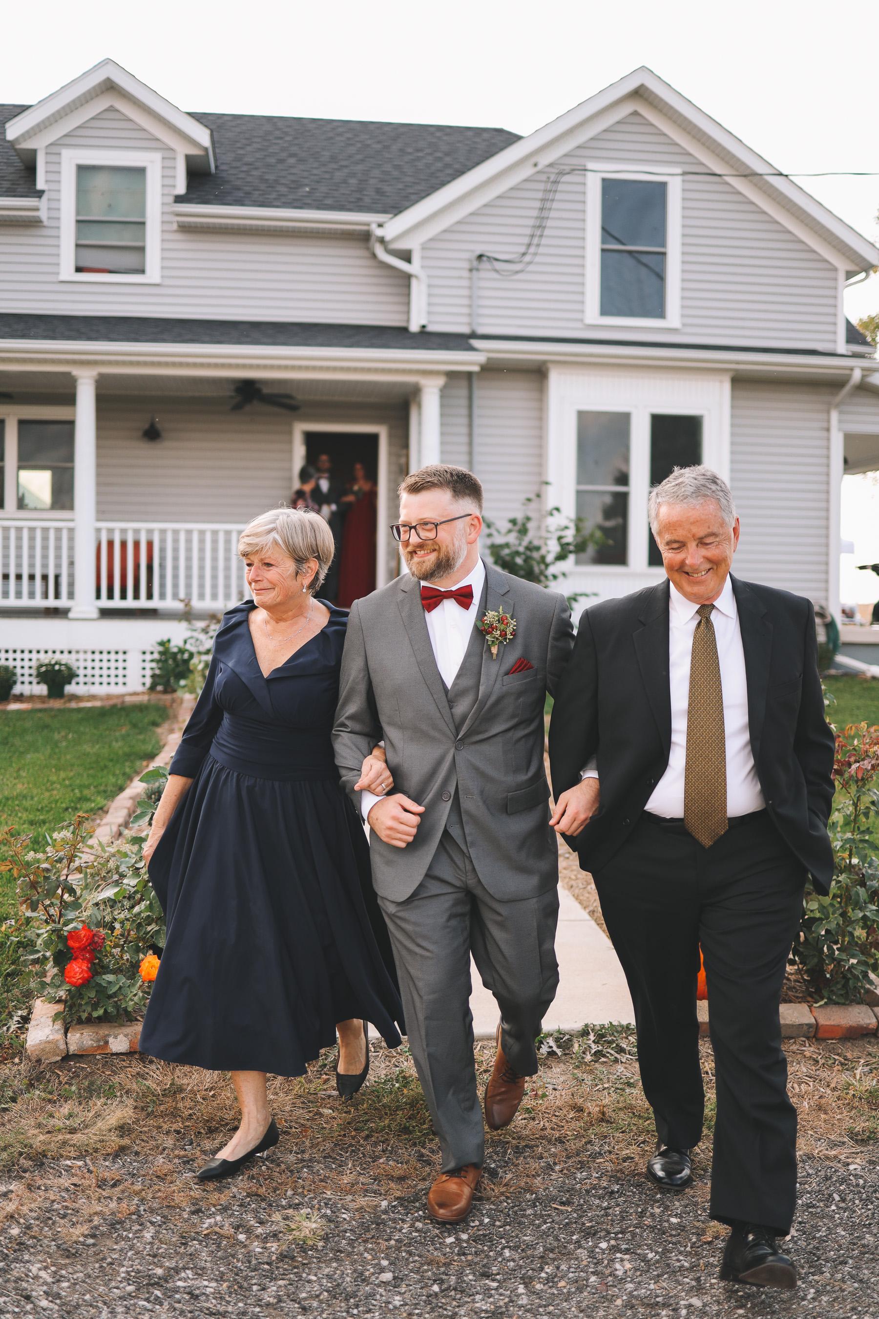 groom walks with parents | Charlie and Shirleys Wedding
