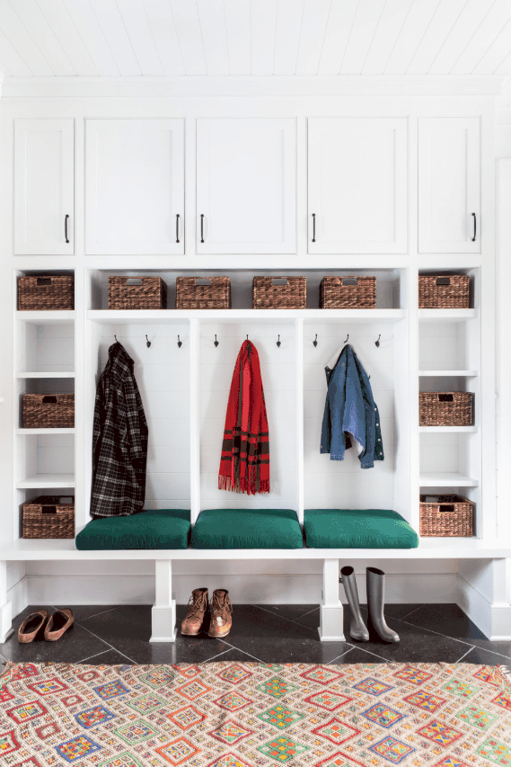small white mudroom with hooks and cabinets