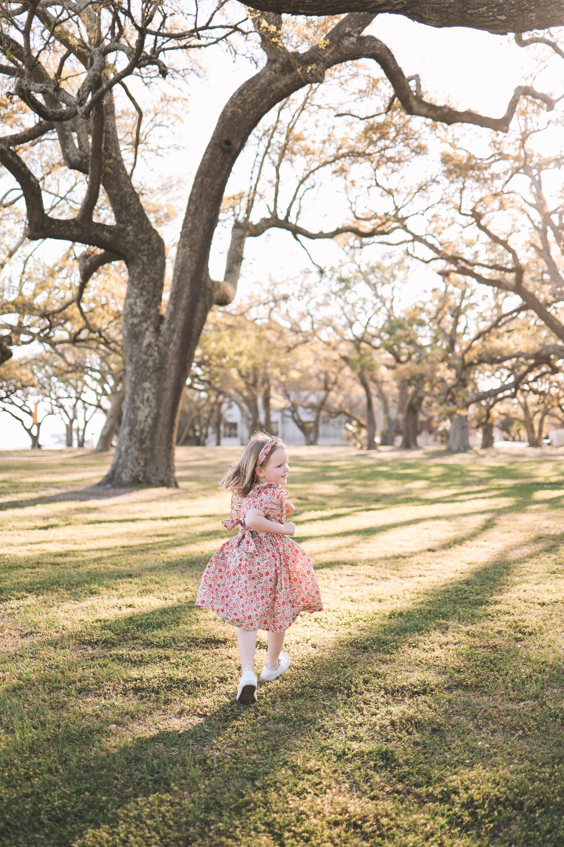 child running around under oak trees