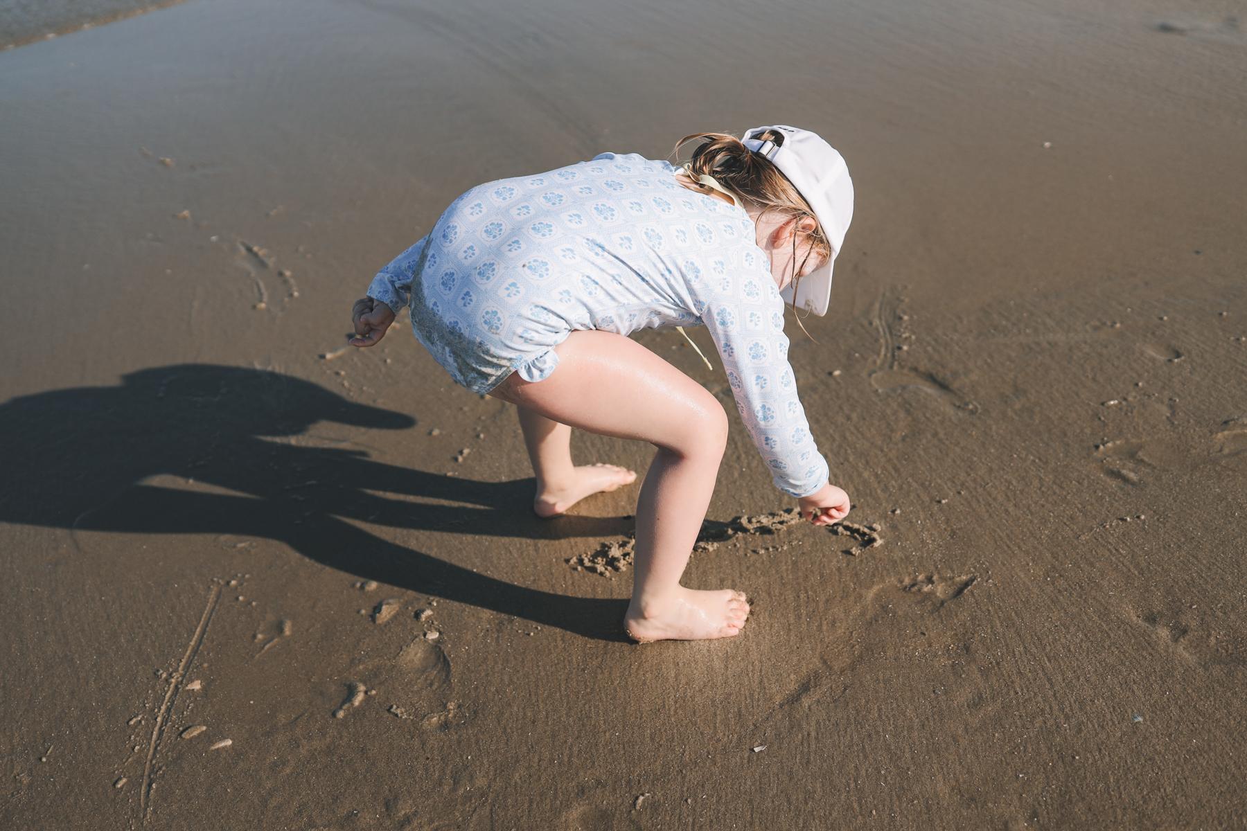 Toddler writing on sand